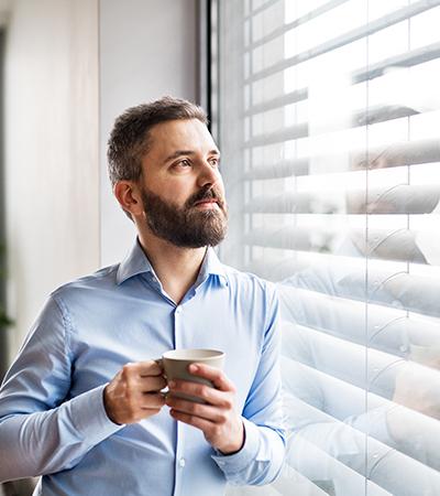 Ein Mann im Hemd mit Kaffee in der Hand guckt aus dem Fenster